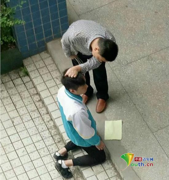 张姓老师手拿带插线板的电线,另一只手揪住跪在地上的学生的头发。